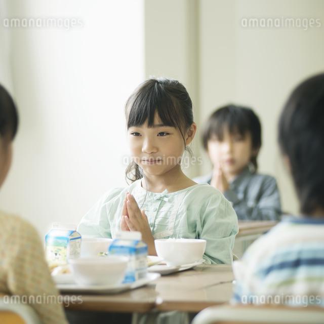 給食を前に手を合わせる小学生の写真素材 [FYI04553592]
