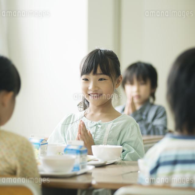 給食を前に手を合わせる小学生の写真素材 [FYI04553593]
