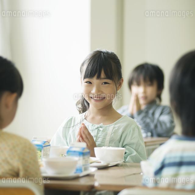 給食を前に手を合わせる小学生の写真素材 [FYI04553594]