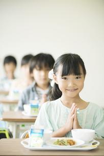 給食を前に手を合わせる小学生の写真素材 [FYI04553595]