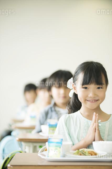 給食を前に手を合わせる小学生の写真素材 [FYI04553596]