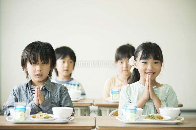 給食を前に手を合わせる小学生の写真素材 [FYI04553601]