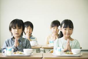 給食を前に手を合わせる小学生の写真素材 [FYI04553602]