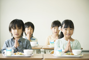 給食を前に手を合わせる小学生の写真素材 [FYI04553603]