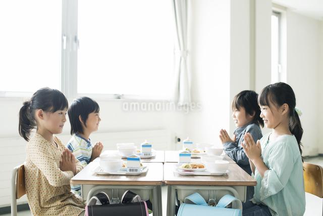 給食を前に手を合わせる小学生の写真素材 [FYI04553604]