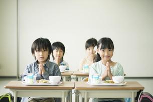 給食を前に手を合わせる小学生の写真素材 [FYI04553605]
