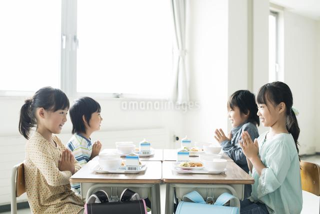 給食を前に手を合わせる小学生の写真素材 [FYI04553606]