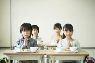 給食を前に手を合わせる小学生の写真素材 [FYI04553607]