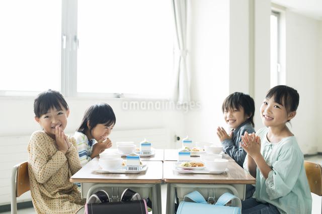 給食を前に手を合わせる小学生の写真素材 [FYI04553608]