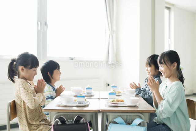 給食を前に手を合わせる小学生の写真素材 [FYI04553609]