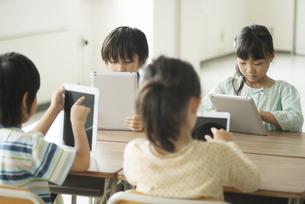タブレットPCを操作する小学生の写真素材 [FYI04553621]