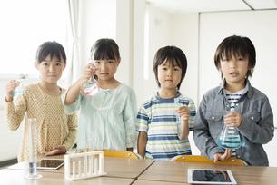 実験器具を持つ小学生の写真素材 [FYI04553694]