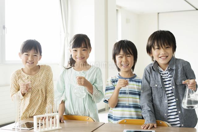 実験器具を持つ小学生の写真素材 [FYI04553696]