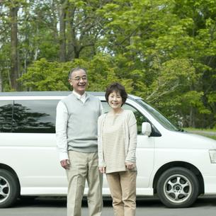 車の前で微笑むシニア夫婦の写真素材 [FYI04553754]