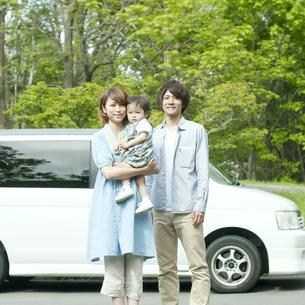 車の前で微笑む家族の写真素材 [FYI04553757]