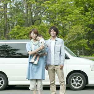 車の前で微笑む家族の写真素材 [FYI04553758]