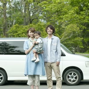 車の前で微笑む家族の写真素材 [FYI04553760]
