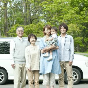 車の前で微笑む3世代家族の写真素材 [FYI04553761]
