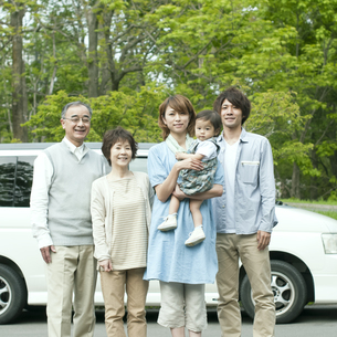 車の前で微笑む3世代家族の写真素材 [FYI04553764]