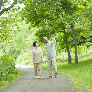 新緑の中を歩くシニア夫婦の写真素材 [FYI04553779]