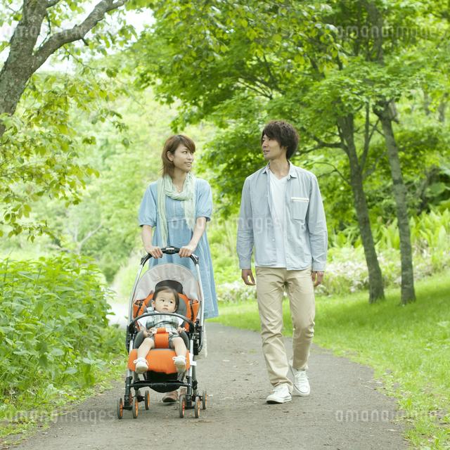 新緑の中を歩く家族の写真素材 [FYI04553781]