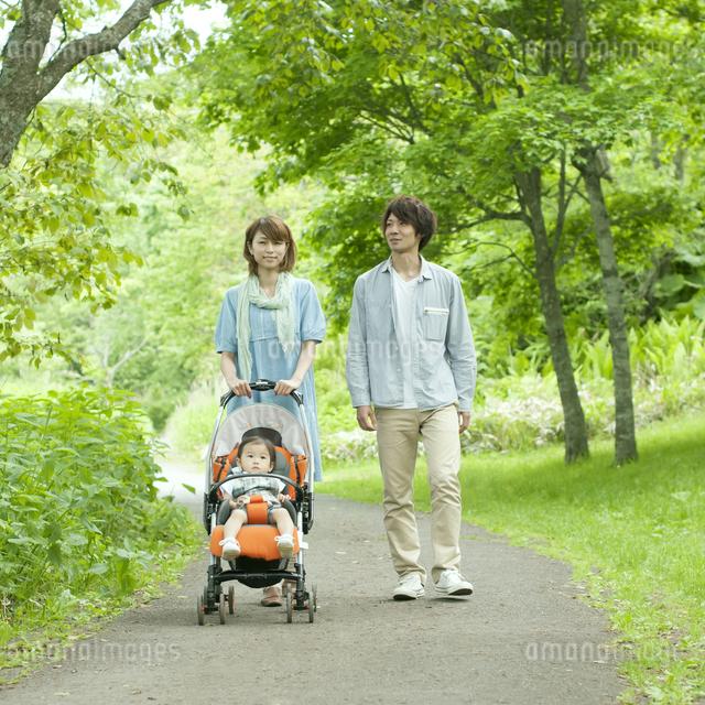 新緑の中を歩く家族の写真素材 [FYI04553782]