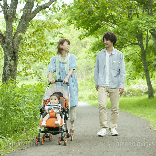 新緑の中を歩く家族の写真素材 [FYI04553785]