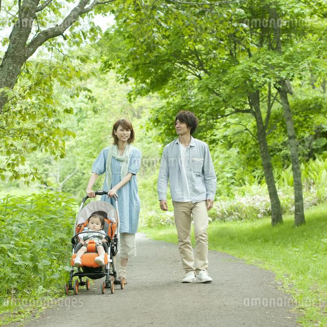 新緑の中を歩く家族の写真素材 [FYI04553786]