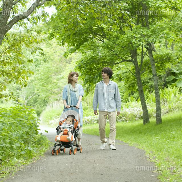 新緑の中を歩く家族の写真素材 [FYI04553787]