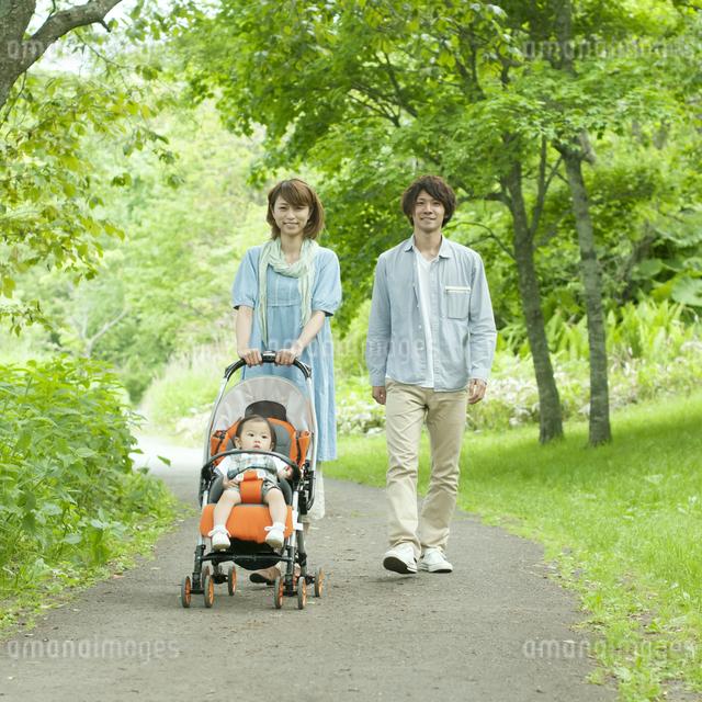 新緑の中を歩く家族の写真素材 [FYI04553789]