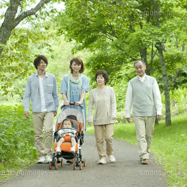 新緑の中を歩く3世代家族の写真素材 [FYI04553791]
