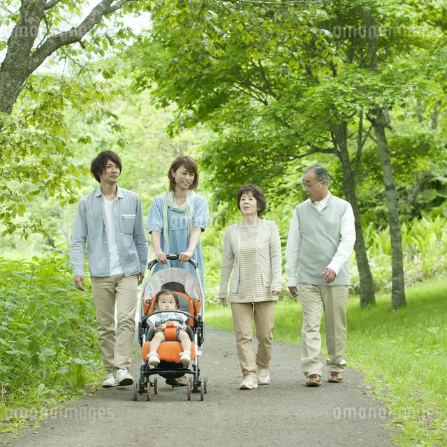 新緑の中を歩く3世代家族の写真素材 [FYI04553792]