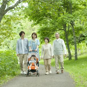 新緑の中を歩く3世代家族の写真素材 [FYI04553793]