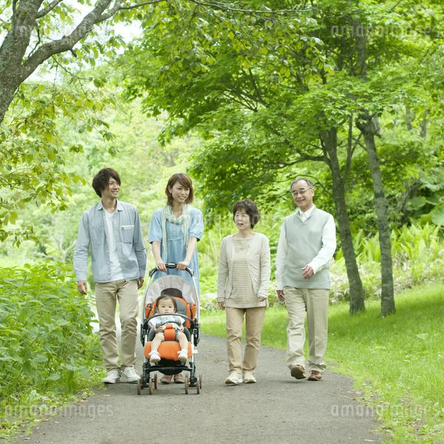 新緑の中を歩く3世代家族の写真素材 [FYI04553794]