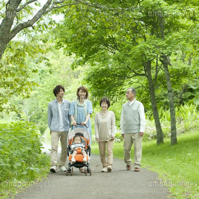 新緑の中を歩く3世代家族の写真素材 [FYI04553795]