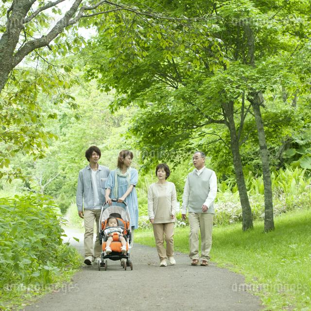 新緑の中を歩く3世代家族の写真素材 [FYI04553796]