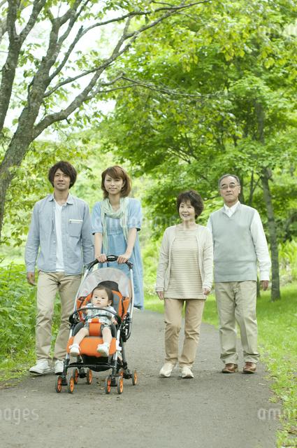 新緑の中を歩く3世代家族の写真素材 [FYI04553797]
