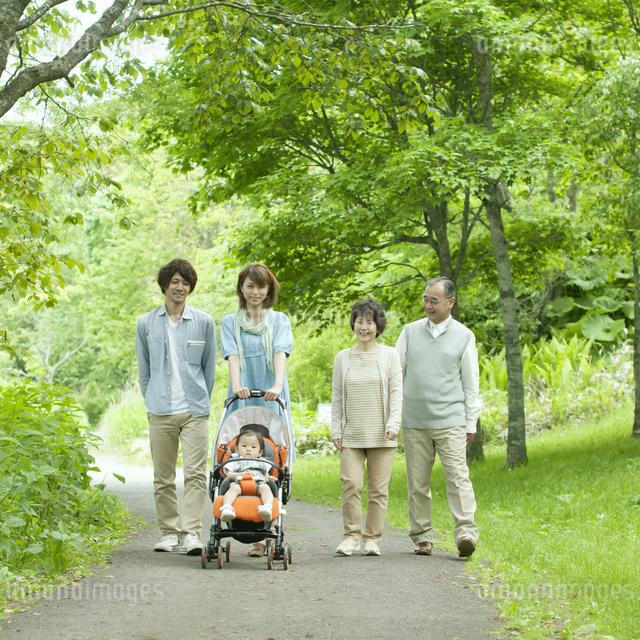 新緑の中を歩く3世代家族の写真素材 [FYI04553799]