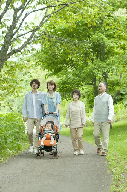 新緑の中を歩く3世代家族の写真素材 [FYI04553800]
