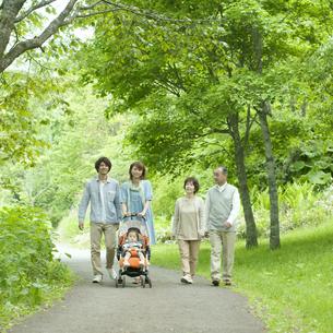 新緑の中を歩く3世代家族の写真素材 [FYI04553802]