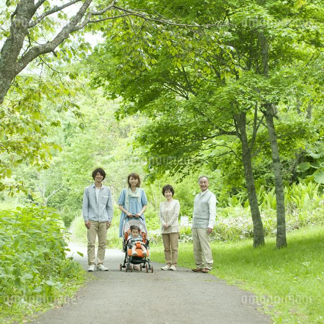 新緑の中で微笑む3世代家族の写真素材 [FYI04553805]