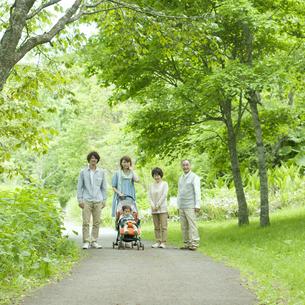 新緑の中で微笑む3世代家族の写真素材 [FYI04553806]