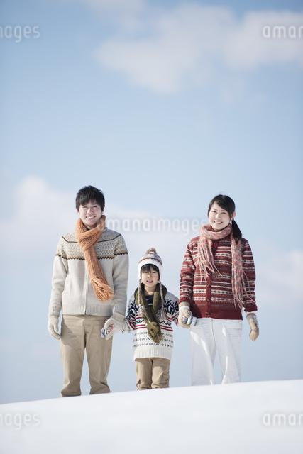 雪原で手をつなぐ家族の写真素材 [FYI04553810]