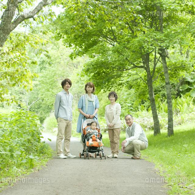 新緑の中で微笑む3世代家族の写真素材 [FYI04553811]