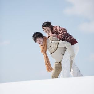 雪原でおんぶをするカップルの写真素材 [FYI04553828]