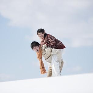 雪原でおんぶをするカップルの写真素材 [FYI04553829]