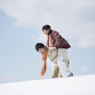 雪原でおんぶをするカップルの写真素材 [FYI04553830]
