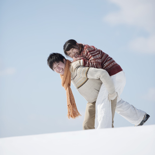 雪原でおんぶをするカップルの写真素材 [FYI04553831]