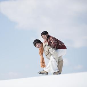 雪原でおんぶをするカップルの写真素材 [FYI04553832]