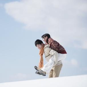 雪原でおんぶをするカップルの写真素材 [FYI04553833]